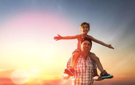 viaje familia: familia feliz en la puesta del sol. padre e hija que se divierte y que juega en la naturaleza. el niño se sienta en los hombros de su padre.
