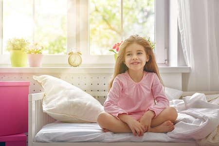 Het kind meisje werd wakker en geniet van de ochtendzon. Stockfoto