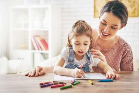 niño escuela: Familia feliz. Madre e hija juntas pintan. Mujer adulta que ayuda a que el niño de la muchacha.