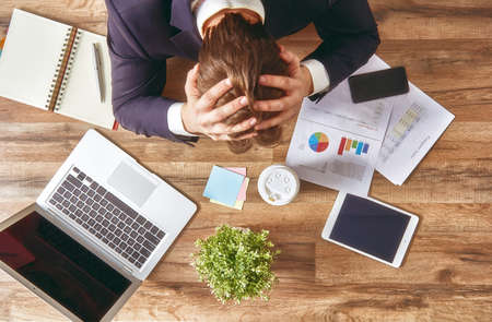 frustrated man: businessman in panic. a young man sits at his Desk and holds his hands on his head. Stock Photo