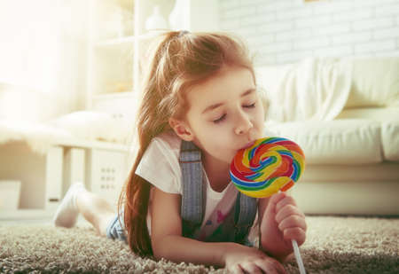 family playing: funny child girl plays at home. girl eating candy and resting. recreation and entertainment at home.