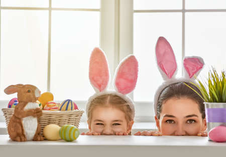 Happy easter! Mother and daughter begin to hunt for Easter eggs. Happy family preparing for Easter. Cute little child girl wearing bunny ears on Easter day. Imagens - 52020220