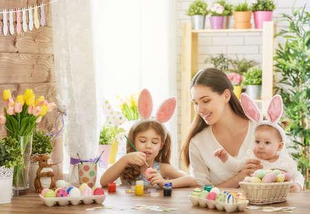 幸せなイースター!母と娘はイースターの卵をペイントします。幸せな家族は、イースターのための準備します。かわいい子女の子のイースターの日