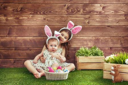 osterhase: Frohe Ostern! Nette kleine Kinder Mädchen tragen Bunny Ohren auf Ostern Tag. Schwestern der Jagd nach Ostereier auf dem Rasen in der Nähe des Hauses. Mädchen, die Spaß, Spielen und umarmt.