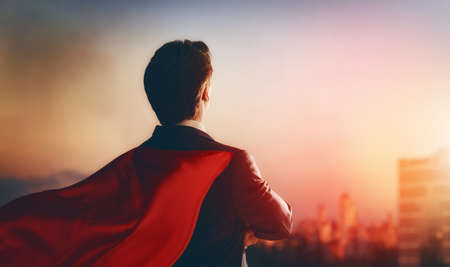 superhero businessman looking at city skyline at sunset. the concept of success, leadership and victory in business. Standard-Bild