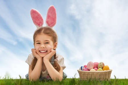 Cute little child girl wearing bunny ears on Easter day. Girl hunts for Easter eggs on the lawn. Girl has basket with painted eggs.