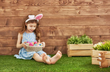 Cute little child girl wearing bunny ears on Easter day. Girl hunts for Easter eggs on the lawn near the house. Girl holding basket with painted eggs. 版權商用圖片