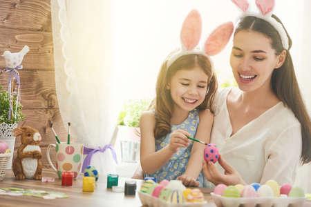 Frohe Ostern! Eine Mutter und ihre Tochter Bemalen von Ostereiern. Glückliche Familie für Ostern vorbereitet. Nettes kleines Kind Mädchen mit Hasenohren auf Ostern Tag. Standard-Bild - 52031350