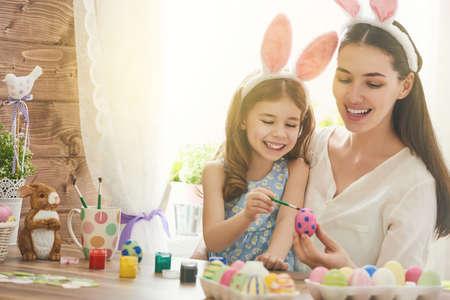 beautiful rabbit: Happy easter! A mother and her daughter painting Easter eggs. Happy family preparing for Easter. Cute little child girl wearing bunny ears on Easter day.