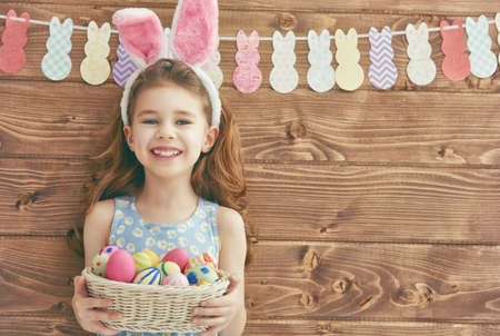 fun colors: Cute little child girl wearing bunny ears on Easter day. Girl holding basket with painted eggs. Stock Photo