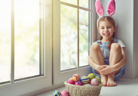 Happy Easter! Cute little child girl wearing bunny ears on Easter day. Girl sitting on the window with a basket of Easter eggs. Child girl laughs and enjoys spring and a holiday.