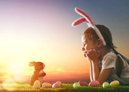 Cute little child girl wearing bunny ears on Easter day. Girl hunts for Easter eggs on the lawn. Girl with Easter eggs and bunny in the rays of the setting sun.