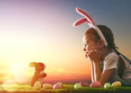 chicas sonriendo: niña niño lindo con orejas de conejo en el día de Pascua. Niña de la caza de los huevos de Pascua en el césped. Muchacha con los huevos de Pascua y conejito en los rayos del sol poniente.
