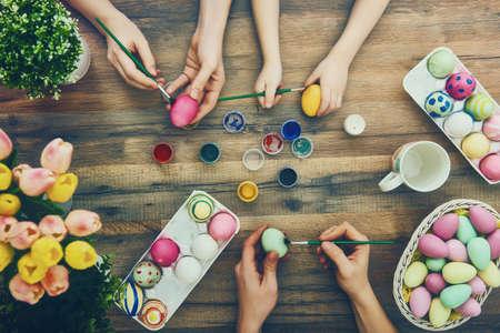 Glad påsk! En mamma, pappa och deras dotter måla påskägg. Lycklig familj förbereder sig för påsk.