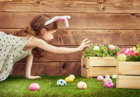 Feliz Páscoa! menina da criança pequena bonito que veste as orelhas do coelho no dia de Páscoa. Menina caça aos ovos de Páscoa no gramado perto da casa. Imagens