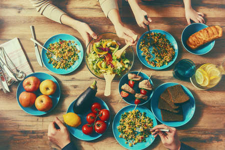 comiendo: Vista superior de la cena con la familia juntos sentados en la mesa de madera rústica. Disfruta de una cena de la familia juntos.