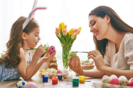 부활절 축복 받으세요! 어머니와 부활절 달걀 그림 그녀의 딸. 부활절을 준비하는 행복한 가족입니다. 부활절 날에 토끼 귀를 입고 귀여운 꼬마 소녀.