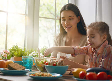 gente comiendo: Cena de familia feliz juntos sentados en la mesa de madera rústica. La madre y su hija disfrutando de la cena de la familia juntos.