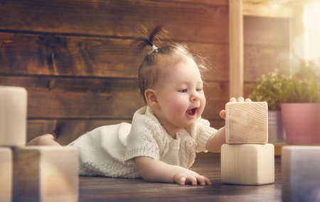 designer baby: happy child  baby girl playing with blocks and having fun.
