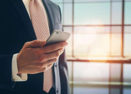 Portret mężczyzny pewność. Przedsiębiorca działa na telefon, stojąc w nowoczesnym inter biurowego. Inteligentny mężczyzna telefonu prawnika gospodarstwo. Zdjęcie Seryjne