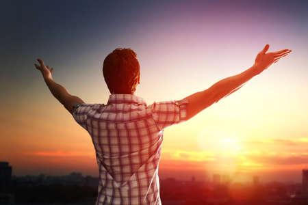 Erfolgreiche Mann auf der Suche bis zum Sonnenuntergang Himmel feiern genießen die Freiheit. Positive menschliche Emotionen Gefühl Leben Wahrnehmung Erfolg, Ruhe Konzept. Freie glücklicher Mann