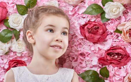 mignonne petite fille: Portrait d'une belle fille mignonne d'enfant sur le fond de fleurs.