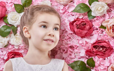 Portrait of a cute beautiful child girl on the background of flowers.