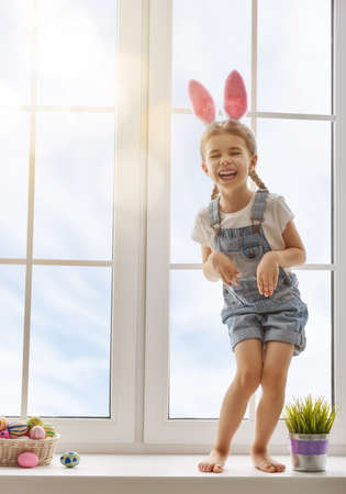 girl sitting: Happy Easter! Cute little child girl wearing bunny ears on Easter day. Girl sitting on the window with a basket of Easter eggs. Child girl laughs and enjoys spring and a holiday.