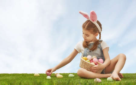little people: Cute little child girl wearing bunny ears on Easter day. Girl hunts for Easter eggs on the lawn. Girl has basket with painted eggs.