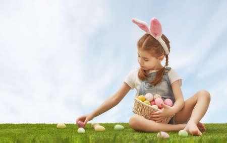 ni�as peque�as: ni�a ni�o lindo con orejas de conejo en el d�a de Pascua. Ni�a de la caza de los huevos de Pascua en el c�sped. La muchacha tiene cesta con huevos pintados.