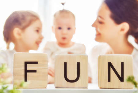 mum and child: Happy loving family playing with blocks and having fun. Blocks have letters. Mother and her daughters lay out cubes and word fun.