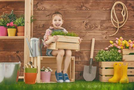 La ragazza sveglia del bambino la cura per le piante. Carino bambina in possesso di una scatola di piante in piedi nel cortile di casa. concetto di primavera, la natura e la cura.