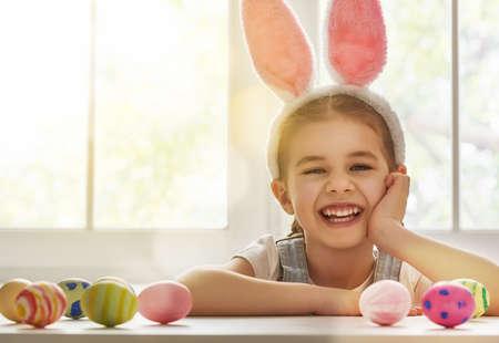 ni�as peque�as: �Felices Pascuas! ni�a ni�o lindo con orejas de conejo en el d�a de Pascua. La muchacha del ni�o se r�e y disfruta de la primavera y un d�a de fiesta.