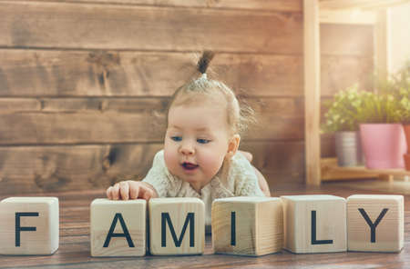 designer baby: Happy child baby girl playing with blocks and having fun. Blocks have letters. The child puts the word Family. Stock Photo