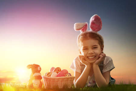 little colours: Cute little child girl wearing bunny ears on Easter day. Girl hunts for Easter eggs on the lawn. Girl with Easter eggs and bunny in the rays of the setting sun.