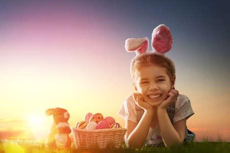 mignonne petite fille: Cute petite fille de l'enfant portant des oreilles de lapin le jour de P�ques. Fille chasse aux ?ufs de P�ques sur la pelouse. Fille avec des oeufs de P�ques et de lapin dans les rayons du soleil couchant. Banque d'images