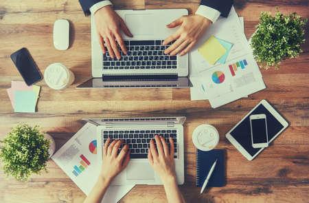 人: 男人和女人的工作在他們的計算機。從頂視圖。兩台筆記本電腦,兩個人。