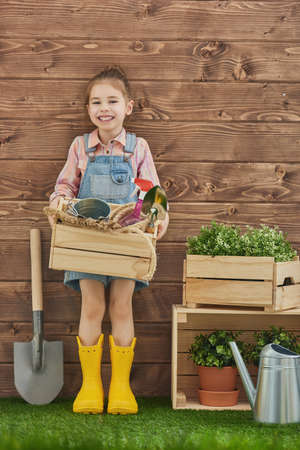 caring for: Cute child girl caring for her plants. Cute little girl holding garden tools standing in the backyard. Spring concept, nature and care.