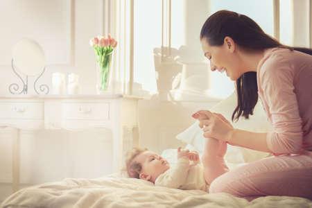 mujer en la cama: familia feliz. madre jugando con su bebé en el dormitorio. Foto de archivo