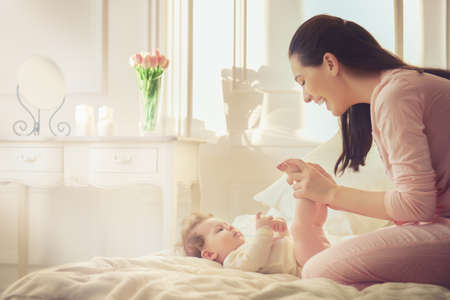 fond of children: happy family. mother playing with her baby in the bedroom.