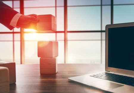 gestion empresarial: El concepto de planificación en los negocios. Cubos de madera en un escritorio en la oficina. El concepto de liderazgo. Hombres de la mano en traje de negocios con los cubos.