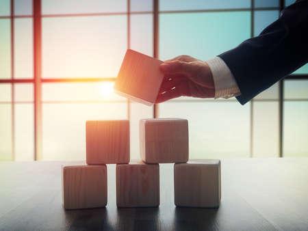Das Konzept der in der Geschäftsplanung. Holzwürfel auf einem Schreibtisch im Büro. Das Konzept der Führung. Hand Männer in Business-Anzug halten die Würfel.