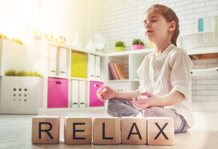 girl child: Little child girl playing with blocks and having fun. Blocks have letters. Child arranges cubes and word Relax. Girl is practicing yoga.