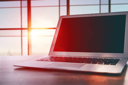 Laptop with dark screen on table in office Foto de archivo