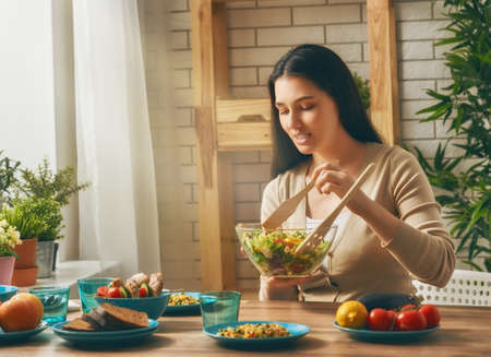 rustic kitchen: a young woman prepares the family dinner.