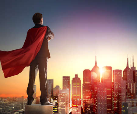 invincible: superhero businessman looking at city skyline at sunset. the concept of success, leadership and victory in business. Stock Photo
