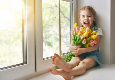 Adorable little child girl sitting on the window and holding tulips. Girl rejoices to spring and sun. Archivio Fotografico