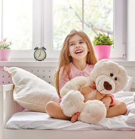 child in bed: The child girl woke up and enjoys the morning sun. Stock Photo