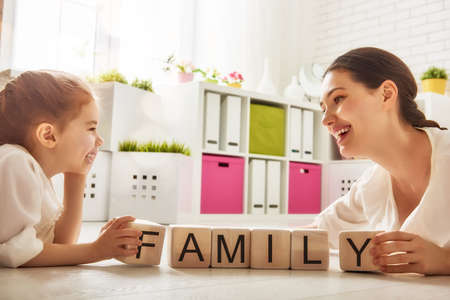 Happy loving family playing with blocks and having fun. Blocks have letters. Mother and her daughter lay out cubes and word family. Фото со стока