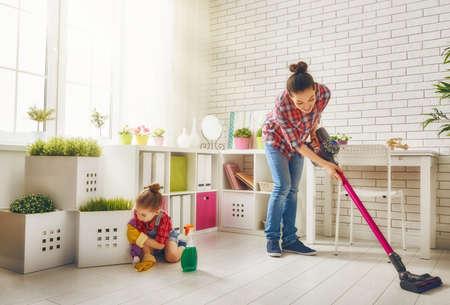 madre trabajadora: Familia feliz que limpia la habitación. Madre e hija hacen la limpieza de la casa. Una mujer joven y una muchacha del pequeño niño se limpió el polvo y aspirar el suelo.